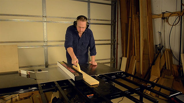 Joshua Farnsworth ripping a board on a SawStop cabinet saw with a SawStop folding outfeed table