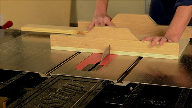 Joshua Farnsworth cross cutting a board on a SawStop cabinet saw with a SawStop folding outfeed table and a cross cut sled
