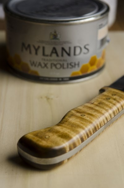 curly maple knife handle with can of Mylands wax in the background