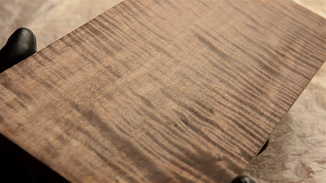 Dark walnut aniline dye coloring a curly maple board