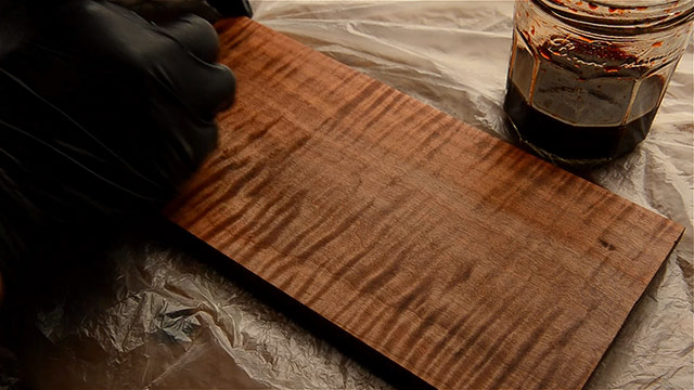 Wiping cherry red aniline dye onto a curly maple board