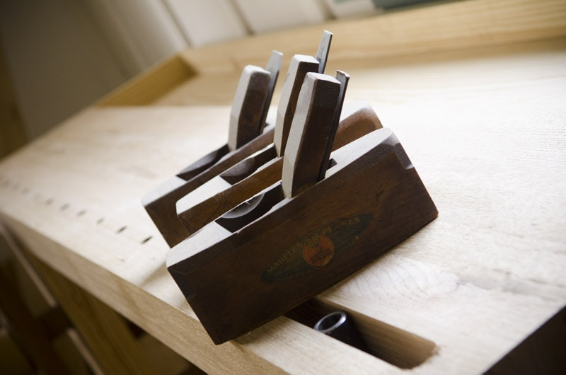 Portable Moravian workbench top with three coffin smoother handplanes on top