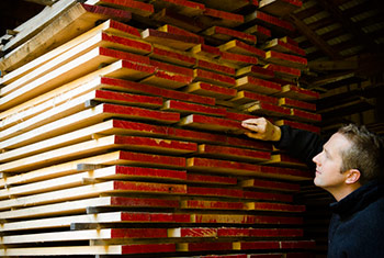 Joshua Farnsworth choosing lumber from a stack of wood with painted end grain