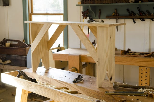 Shaker bench sitting on a workbench for woodworking plans
