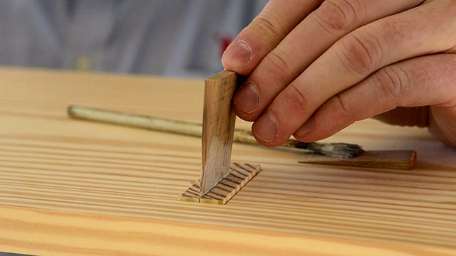 Woodworker gluing a wooden wedge into a wedged tenon for mortise and tenon joints