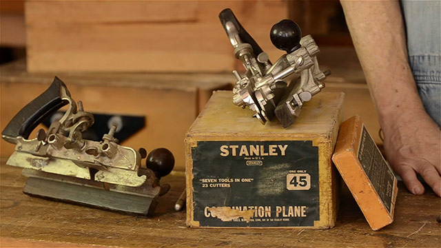 Stanley 45 combination plane box with three combination planes or universal planes on a woodworking workbench