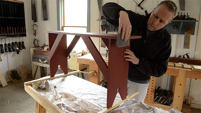 Joshua Farnsworth using sandpaper to smooth between milk paint coats on a Shaker bench with homemade milk paint from scratch
