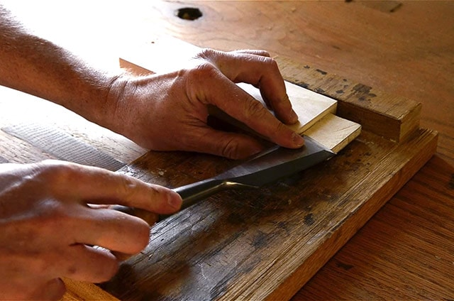 Using a bench hook and a chisel to trim a tenon on a workbench