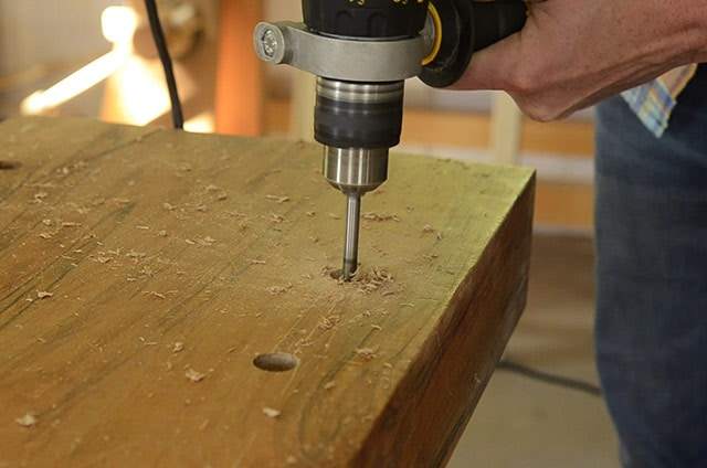 Woodworker Using A Dewalt Drill To Finish Boring A Wooden Workbench Dog Hole On A Portable Moravian Workbench