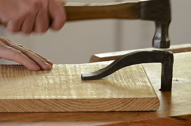 Using a hammer to hit a forged holdfast into a workbench hole