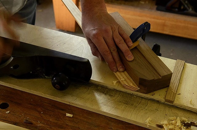 woodworker using a shooting board to trim a mitered piece of molding with a stanley 6 handplane