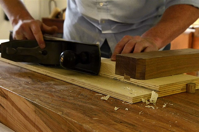 woodworker using a shooting board to trim end grain of a board with a stanley 6 handplane