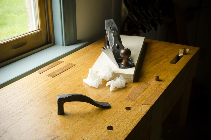 Stanley Bailey Number 4 Smoothing Plane Sitting On A Board With Shavings On A Roubo Workbench With A Forged Holdfast