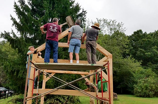 Students Of A Timber Framing Class Using A Large Mallet To Secure Roof