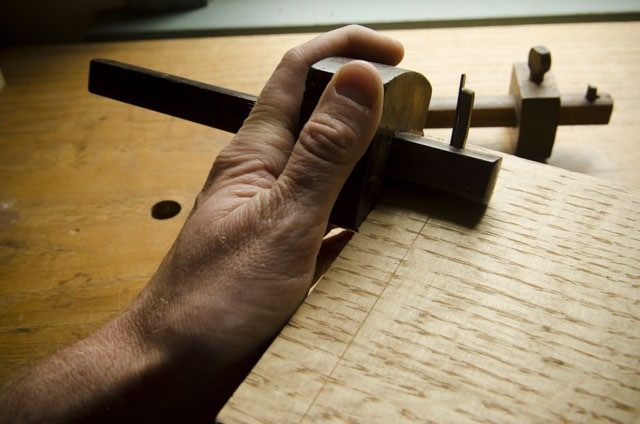 Woodworker Using A Wooden Cutting Gauge Marking Gauge On A Piec Of Figured Quartersawn White Oak Lumber Over A Roubo Woodworking Workbench With Other Marking Gauges In The Background
