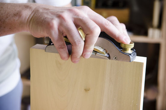 Joshua Farnsworth Using A Lie-Nielsen Rabbet Block Plane To Square The End Grain Of A Board While Squaring Up A Board For Woodworking On A Woodworking Workbench