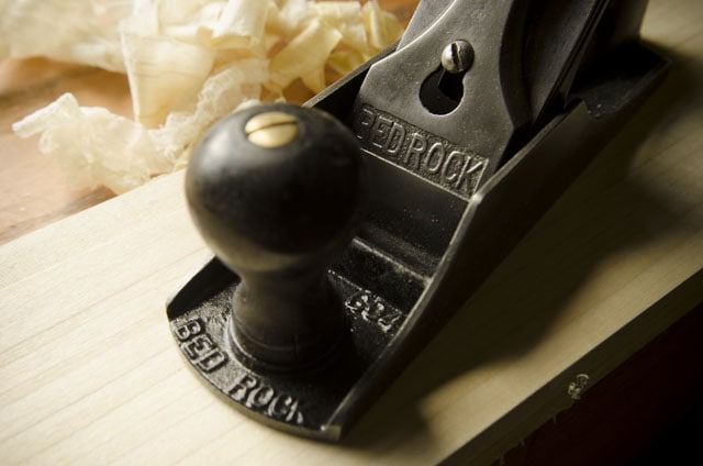 Close Up Of A Stanley Bed Rock 604 Smoothing Plane With Shavings And Board Sitting On A Roubo Workbench