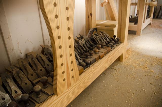An Assortment Of Antique Bench Hand Planes Under A Woodworking Workbench