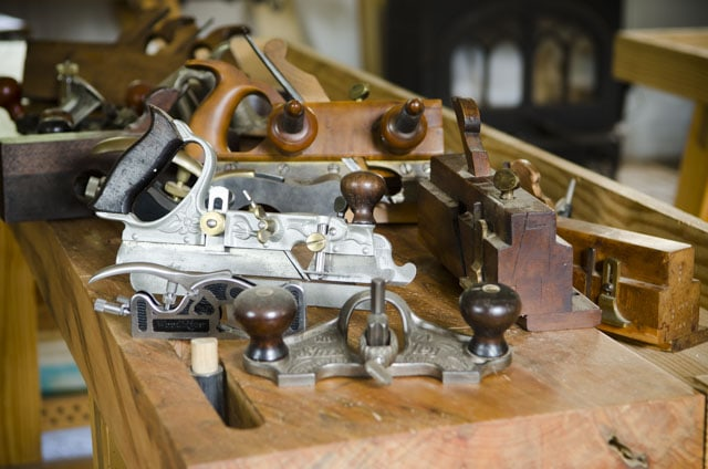A Bunch Of Joinery Planes On A Moravian Workbench Top Including A Router Plane, Plow Plane, And Moving Fillister Plane