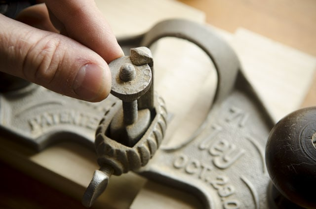 Fingers Microadjusting A Metal Stanley 71 Router Plane With A Dado Joint Below