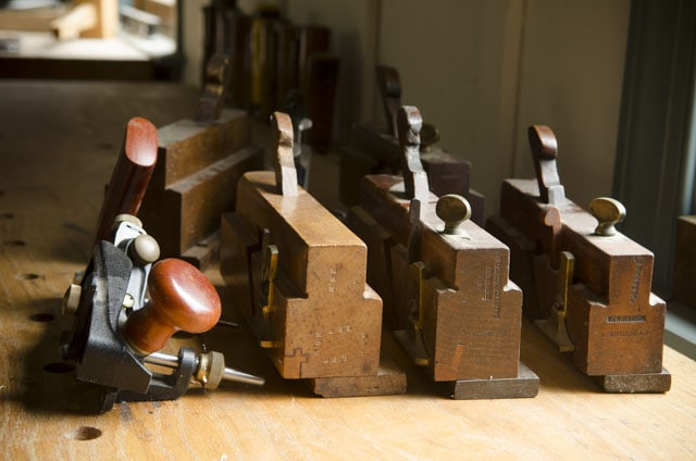 A Row Of Wooden And Metal Moving Fillister Planes On A Roubo Workbench