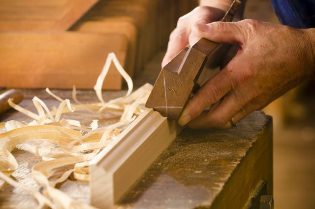 Woodworker using a dedicated molding plane to cut a molding or moulding