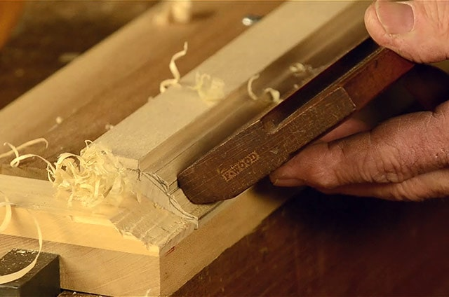 woodworker using a sticking board to hold wood for using hollows and rounds molding planes