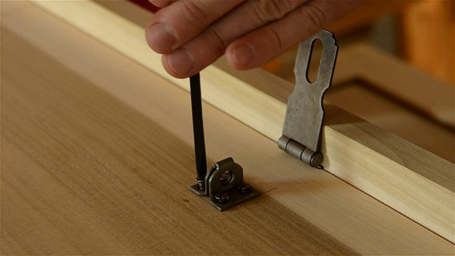 Woodworker Using A Screw Driver To Drive Slotted Wood Screws Into Historical Hasp Hardware Installed On A Dovetail Chest