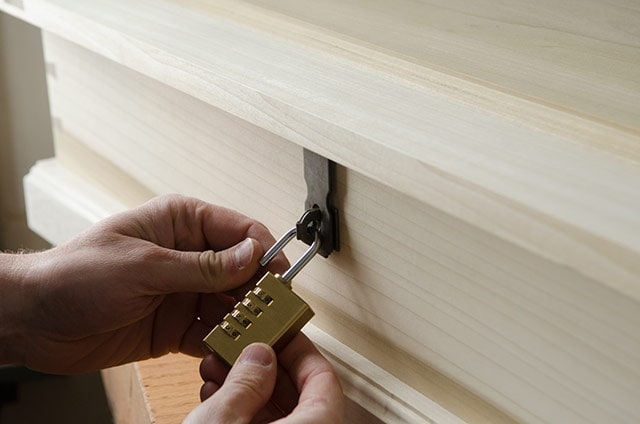 A Woodworker Locking A Brass Padlock On A Hasp On A Wooden Dovetail Chest Box