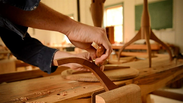 Using a spokeshave to smooth a table leg